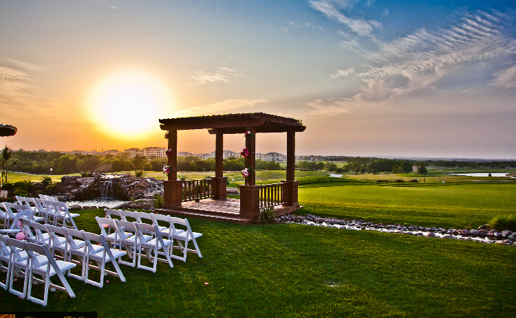 The sun sets behind an outdoor wedding ceremony setup at The Golf Club at Star Ranch